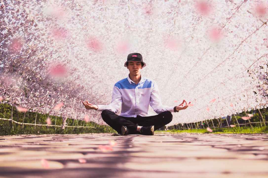 man meditating in the middle of pathway